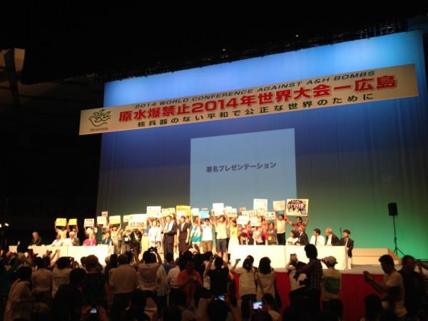 閉会総会でアンゲラ・ケイン国連軍縮上級代表に署名数かかげてプレゼンテーション