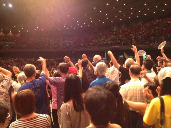 閉会総会の舞台上で若い世代や海外代表たちが熱気あふれるなか、決意あらたに…